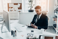 Making some notes. Handsome young man in full suit writing something in his notebook while sitting at the office desk Stock Image