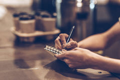 Making some notes. Part of close-up of young woman writing in notebook while standing at bar counter Stock Photos