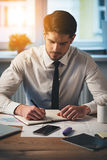 Making some notes. Pensive young handsome man writing in his notebook while sitting at his working place stock photos