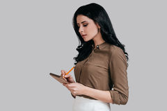 Making some notes. Thoughtful young woman in smart casual wear writing something in her notebook while standing against grey background Royalty Free Stock Photography