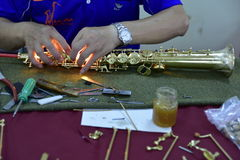 Making soprano saxophone. A technician is assembling some component parts of soprano saxophone. Photography in Houli District;Taichung city, Taiwan Royalty Free Stock Photography