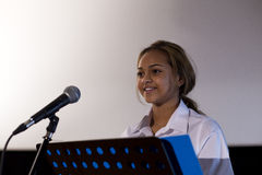 Making a Speech. Female student making a speech. She is standing at a podium and smiling to the crowd Royalty Free Stock Images