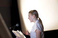 Making a Speech. Female student making a speech. She is standing at a podium and smiling to the crowd Stock Images