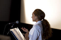 Making a Speech. Female student making a speech. She is standing at a podium and talking to the crowd Stock Photo