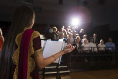 Making a Speech. Female student making a speech. She is standing at a podium and talking to the crowd of people Royalty Free Stock Images