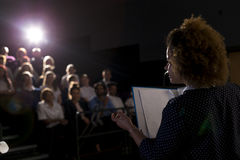 Making a Speech. Female teacher giving a speech in a lecture hall to students and teachers royalty free stock images