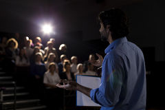 Making a Speech. Male teacher giving a speech in a lecture hall to students and teachers Stock Photo