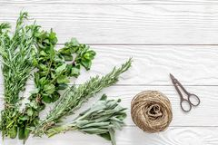 Making spices with fresh herbs and greenery for cooking white wooden kitchen table background top view mockup Royalty Free Stock Photos