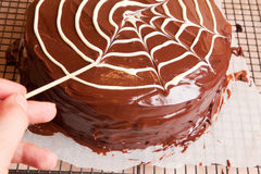 Making spiders web on the chocolate cake Stock Photo