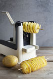 Making spiral potatoes  with a spiralizer machine Royalty Free Stock Photos