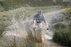 Making a Splash. Cycling through a big puddle, making a big splash. Mountain biking in the Claerwen Valley, Wales Royalty Free Stock Images