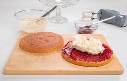 Making sponge cake, cake split spread with jam/preserve putting butter cream in filling in Royalty Free Stock Photo