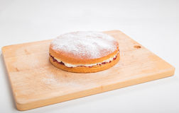 Making sponge cakes, finished cake on with sifted icing sugar Stock Photo