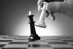 Making a strategic move. Conceptual image depicting making a strategic move with a hand moving a chess piece on a chessboard during a game of skill Stock Photography