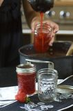 Making Strawberry Jam. A young woman ladles hot strawberry jam into canning jars Royalty Free Stock Photo