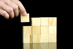 Making a structure with wooden cubes. Making a structure with blank wooden cubes. Isolated over black background Stock Images