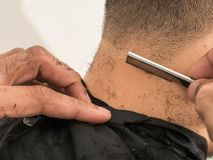 Making stylish haircut at salon close up. barber shaving him with razor. Beauty, modern style, lifestyle, trend concept.  royalty free stock image
