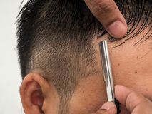 Making stylish haircut at salon close up. barber shaving him with razor. Beauty, modern style, lifestyle, trend concept.  royalty free stock photography