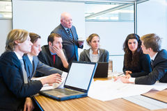 Making a suggestion. The youngest employee making a suggestion during a team meeting, and everybody, including the senior executive (boss) listens stock images