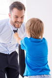 Making sure his father looks good. Playful little boy helping father to tie a necktie stock photo