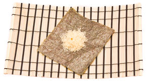 Making Sushi on a bamboo sushi mat Royalty Free Stock Photo