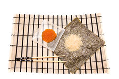 Making Sushi on a bamboo sushi mat Royalty Free Stock Photos