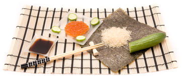 Making Sushi on a bamboo sushi mat Royalty Free Stock Images