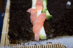 Making sushi. Making delicious maki sushi with salmon, avocado and cucumber Royalty Free Stock Image