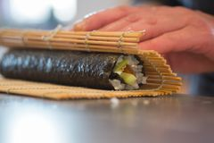 Making  sushi roll with salmon. Rice, cucumber and nori. closeup Royalty Free Stock Photos