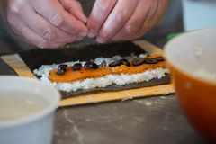 Making sushi roll with salmon. Rice, olives and nori. closeup Royalty Free Stock Photo