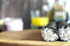 Making Sushi Rolls Workshop. Two Shaped Round Rolls Sealing on a Wooden Board before Slicing. Blurred Shiny Background, stock photo