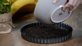 Making sweet tart of the chocolate cookies crumbs. stock video footage