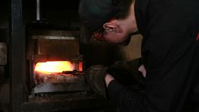 Making the sword out of metal at the forge. Blacksmith pulls out of the furnace hot metal blanks. stock video
