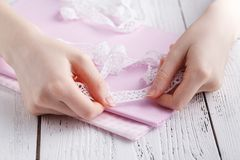 Making table decorations. A shot of woman sewing a natural beige linen tablecloth, towels and napkins with rose print and a croche. T white linen lace trim Royalty Free Stock Image