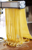 Making tagliatelle with a pasta machine. Royalty Free Stock Photos