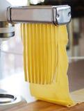 Making tagliatelle with a pasta machine. Stock Photos