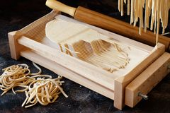Making tagliolini pasta alla chitarra with a tool. Close up Royalty Free Stock Images
