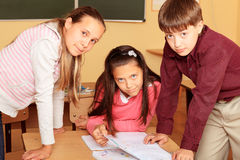 Making a task. Educational theme: schoolchildren in a classroom Stock Images