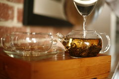 Making tea. Water is being poured into a clear glass tea pot with tea leaves Stock Photo