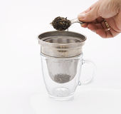 Making tea. Putting tea leaves in tea straine Royalty Free Stock Photos