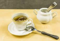 Making tea from a bag in a cup and sugar bowl in the background. royalty free stock images