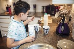 Making Tea at Breakfast. Little boy is helping to make tea for his parents at breakfast time. He is adding sugar to some cups royalty free stock photos