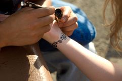 Making temporary, henna tattoo on wirst Stock Images