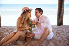 Making a toast with beer at the beach Royalty Free Stock Images