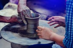 Making it together. close-up to hands of potter teacher and child stock photos