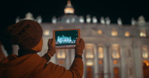 Making touch pad photos of night St. Peters. Night view of St. Peters Basilica in Vatican City. Female tourist using tablet PC to take some photos of famous stock video footage