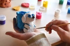 Making toys, paints a pottery clay dog figure with gouache. Indoors creative leisure for children. Supporting creativity, learning Royalty Free Stock Photography