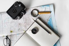 Making a travel plan. Map, blank notepad, camera, magnifier, compass, pencil and glasses Flat lay Royalty Free Stock Image