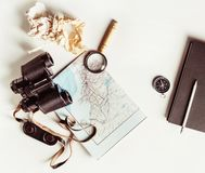 Making a travel plan. Tourist devices on white paper background. Vintage toned image. Top view. Flat lay Stock Photos