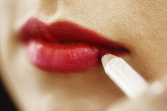 Making up lips with a red pensil Stock Image